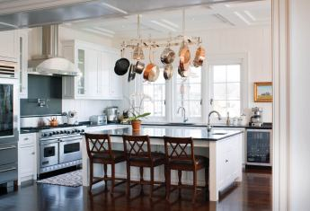 Double-coffered ceilings add interest to the simple white, black and stainless kitchen.