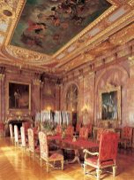 The dining room at Marble House boasts a large mahogany table with gilt pedestals.