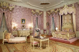 Alva Vanderbilt's bedroom with its silk lampas wall covering and ornamental cherubs, nymphs and gold garlands.