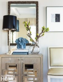A delicate shell mirror and a piece of decorative coral in the entryway subtly reference the coastal location.