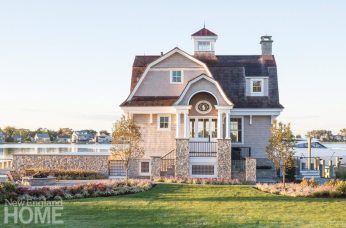 A graceful, cedar-shingled gambrel roof, stone sheathing, bracketed eaves, and a cupola give the diminutive structure the hallmarks of the Shingle style. Sitting on Long Island Sound, the pool house is a stylistic echo of the main house, which overlooks it from its uphill location.