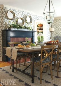 In a play on the traditional mirror above the mantel, designer Karen Bow hung three deep-framed mirrors. An iron-based table with a salvaged wood top is a rustic counterpoint to the contemporary rug.