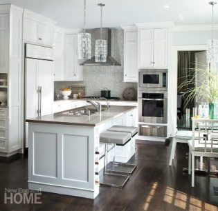 Every inch is maximized in the kitchen, where the work triangle is small, but materials like the velvet quartzite countertops and glass mosaic backsplash loom large.