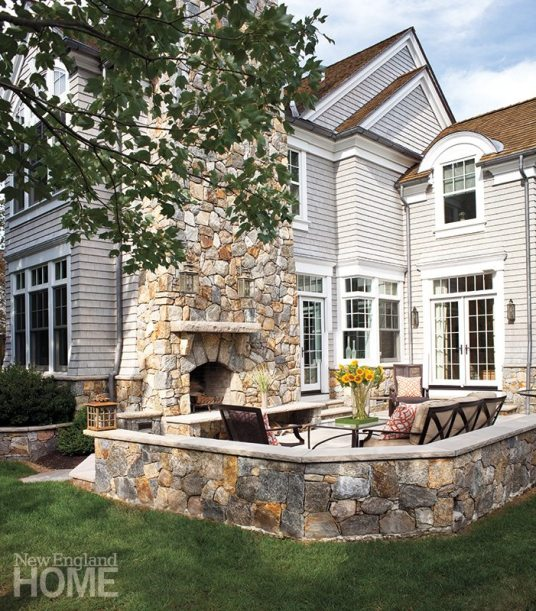Stone walls echo the water table that surrounds the house, defining a cozy patio; the sky-high fireplace adds drama, while hanging lanterns reflect the designer's love of purposeful lighting.