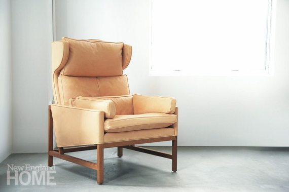 A simple wood frame grounds the layered cushions of the reinterpreted Wingback Lounge Chair