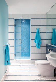 Strips of iridescent glass tile shimmer against white granite in the bathroom.