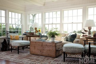 Comfy seating surrounds an antique chest turned coffee table in the sitting room adjacent to the kitchen.
