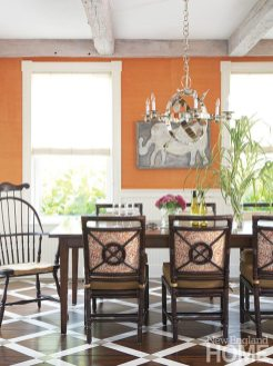 The dining chairs' hand-screened Galbraith & Paul fabric picks up the tangerine hue on the walls. The primitive elephant painting is from Nantucket Looms.
