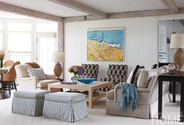 An oil painting by American artist Megan Hinton, a focal point of a seating area in the living room, picks up the blue of the ottomans and accessories.