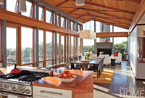 Cherry kitchen cabinetry, a fir ceiling and windows and a bright rug under the dining room table banish all hints of glassy coldness.