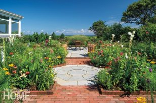 A cutting garden planted in parterre fashion surrounds a brick and bluestone pat