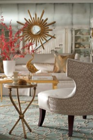 Designer Michelle Morgan Harrison brought drama to the living room with a wall of antiqued mirrored panels and glamorous materials like the silvery white sofa fabric and the combination of a silver-and-white patterned fabric from David Hicks and a metallic linen from F. Schumacher on the chairs.