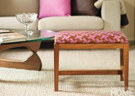 A bench, in natural walnut, wears a bespoke weave in Chocolate and Bougainvillea.