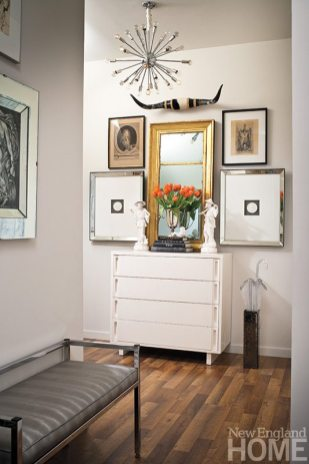 A lacquered cabinet provides an anchor for artwork in the entryway.