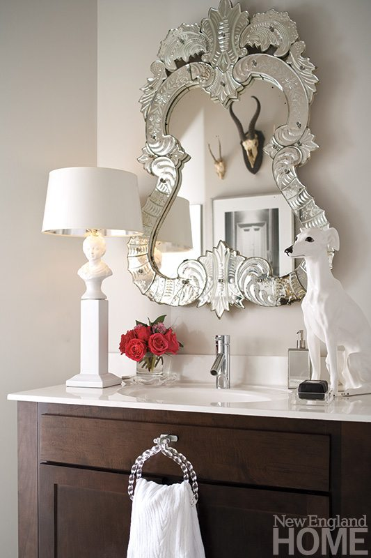 In the powder room, a Venetian mirror, slender lamp and ceramic dog add scale to what might otherwise be a forgettable space.