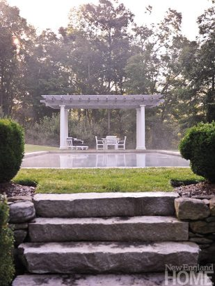 The pretty woodland garden is situated beyond the pool and pergola.