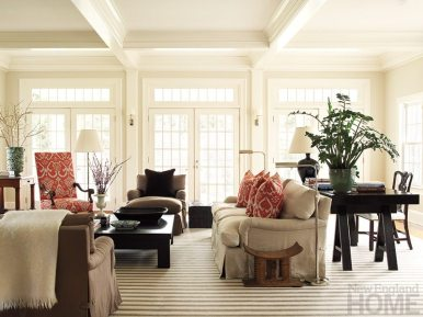 A smattering of well-placed color enlivens the family room without upsetting the neutral palette's serenity. Accessories are primarily limited to books and natural elements like green plants and pickings from the garden to maintain the airy ambience. A saw-horse table by Waldo's Designs serves as a handy desk, while John Boone's upholstered club chairs and welcoming sofa guarantee comfort.