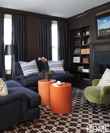 """Saturated colors in carpet and upholstery, dark blue silk window treatments, mahogany paneling and an emphasis on warmth and comfort create what designer and homeowner Katherine Hodge calls her """"winter room."""" Pops of color enliven the small space."""