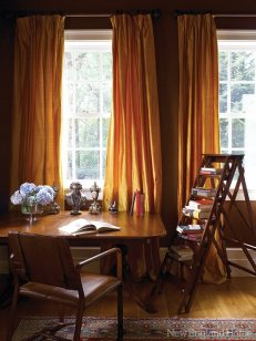 Cocoa-colored walls and gold silk curtains make for a sumptuous study.