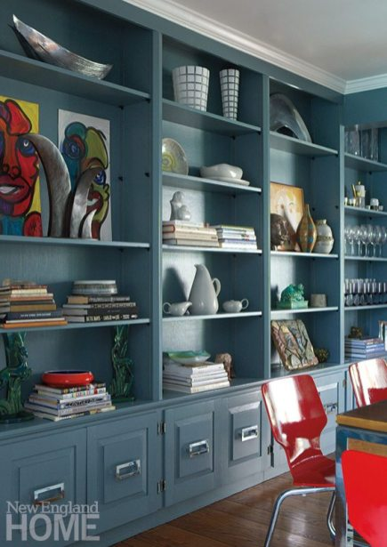 The dining room's existing built-ins were given new hardware and painted teal, and now hold designer/homeowner Denise Davies's collection of midcentury pottery and art books.