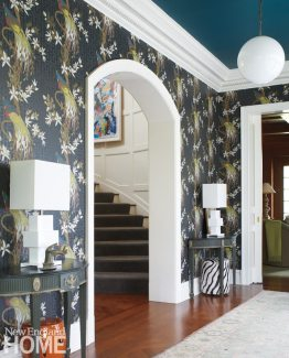 The rear foyer gets dramatic with a peacock-blue ceiling and Nina Campbell's Paradiso wallpaper.