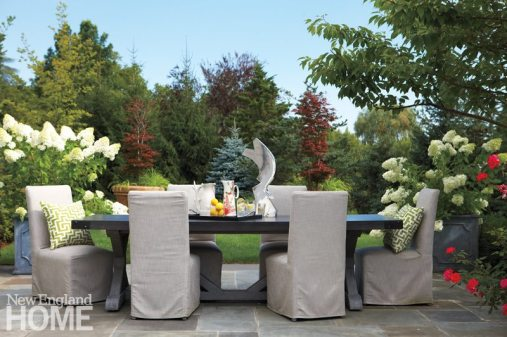The pretty outdoor dining area features a zinc-topped table and chairs covered in sturdy outdoor fabric.