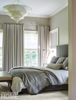 Gray-blue makes a serene palette for the master bedroom; the tiered chandelier is by Oly.