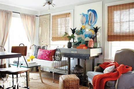 Fearless about mixing styles and textures, Bee outfitted the sitting area off the kitchen with a distressed iron daybed, a plush upholstered Empire-style chair, and a rustic stone-topped table, above which hangs a painting by New York artist Eliska Smiley.