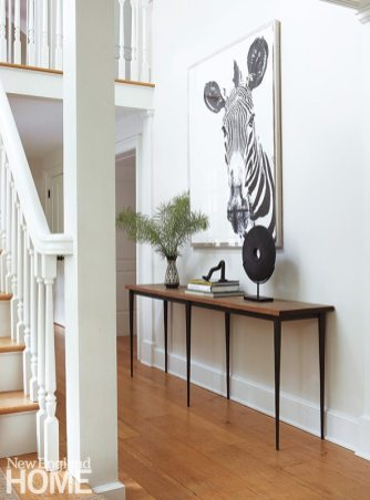 A white-on-white hallway is punctuated by a sleek console and graphic zebra painting.