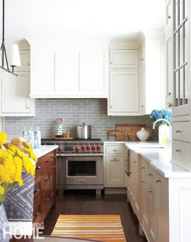 Gray tile from Waterworks makes for a sophisticated backsplash below custom cabinets painted in Farrow & Ball's popular Clunch. A walnut island provides warm contrast with the marble counters