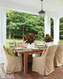 A Restoration Hardware dining table is surrounded by chairs slip-covered in an all-weather fabric by Lee Industries.