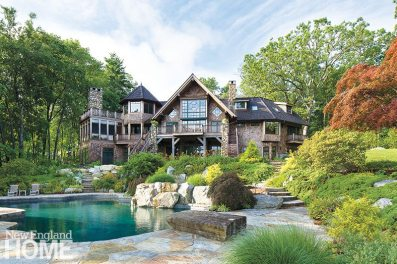 The main house overlooks the lake and the swimming pool from its balconies, enormous windows, a tower, and a large screened porch.