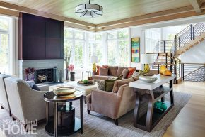 The family room features a bluestone fireplace topped by a bronze-finished steel panel system that hides a television.