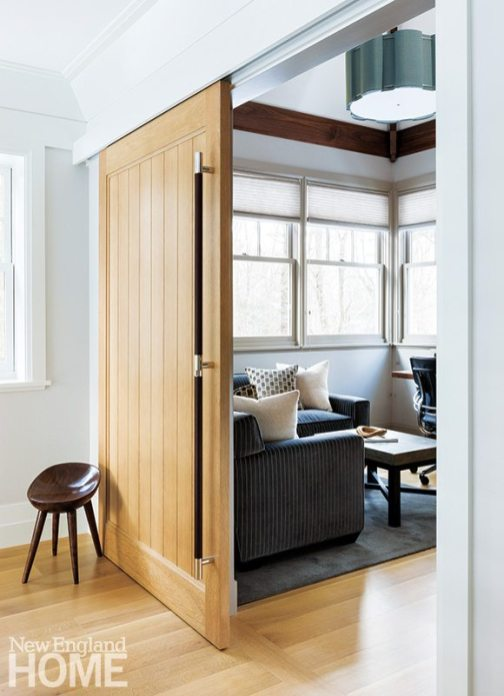 An oak barn door with a handsome leather pull opens to a second-floor office.