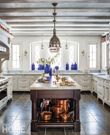 Kitchen designer Nena Donovan Levine tailored the layout to the way the owners work in the space. The cabinets and marble-topped island, inspired by Welsh furniture, showcase the couple's cobalt glass and copper pots.