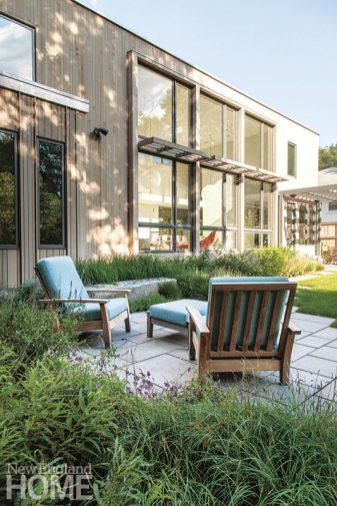 Rear sitting areas are tucked to the side to allow an unimpeded view of the lawn through the broad windows.
