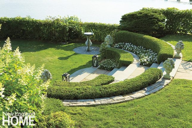 Boxwoods, statuary, and white flowers give the garden its classic feel.