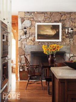 The kitchen's reproduction Windsor chairs are in keeping with the clients' desire for a home with tradition; the tole sconces were custom-designed to complement the stone fireplace wall.