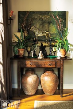 Charming vignettes, like this antique Brazilian Peroba table hosting antique Buddhas and sheltering antique Brazilian pots, abound. The addition of a contemporary Dutch painting further elevates the composition's eye appeal.