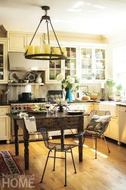 Glass-front cabinets help keep the kitchen feeling airy, while honed granite counters provide a work surface.
