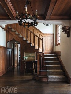 The entry's original woodwork and chandelier are testaments to the home's pedigreed past. Atop the antique table rests an 1899 painting of Lake George, New York, bought at an auction.