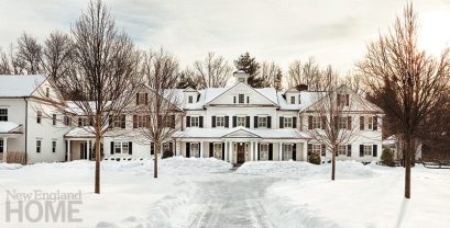 The newly renovated home is unified by a lengthy front porch and features such traditional colonial design elements as a cedar-shingle gabled roof and dormers.