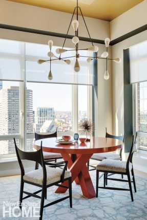 Hammered-gold wallpaper on the ceiling of the dining area adds texture and warmth to the room without being glitzy.