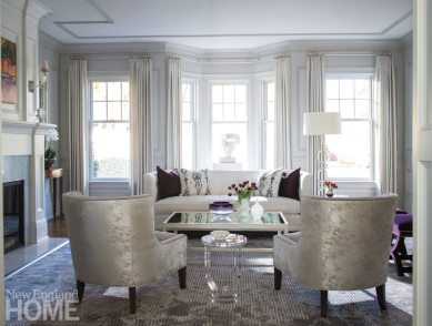 Silvery chairs frame a view of the sofa and a sculpture in the window overlooking the front lawn.