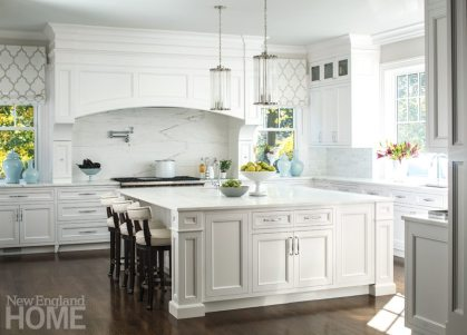A custom hood and island are commanding elements in the bright white kitchen.