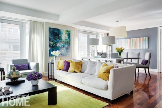Designer Kristen Rivoli took cues from Kathy Soles's vivid painting Deep Water to form the palette for the living room and dining area. The homeowners' own discoveries, like the gold and jade Thai vessel on the coffee table, bring a personal touch to the space.