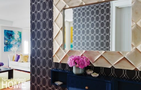 The diamond pattern of the silvery mirror frame plays off the silver circles in the foyer's wallpaper.