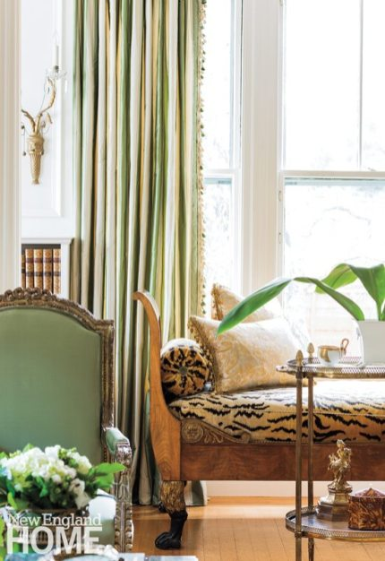 Antique gilded-wood sconces and an antique brass-rimmed table add a layer of interest to the living room alcove. The Louis XVI chair is one of two flanking the antique coffee table.