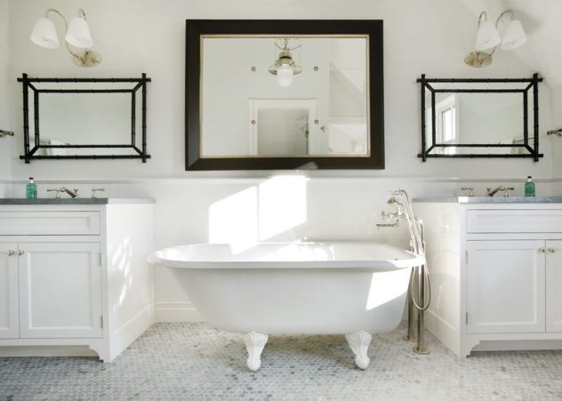 This white-tiled bathroom, with its twin vanities and claw-foot tub, is also part of the upstairs master suite.