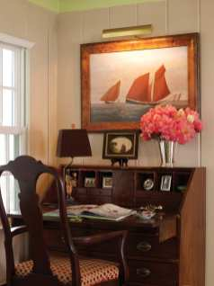 An antique secretary in one corner of the living room offers a civilized space for bill paying.